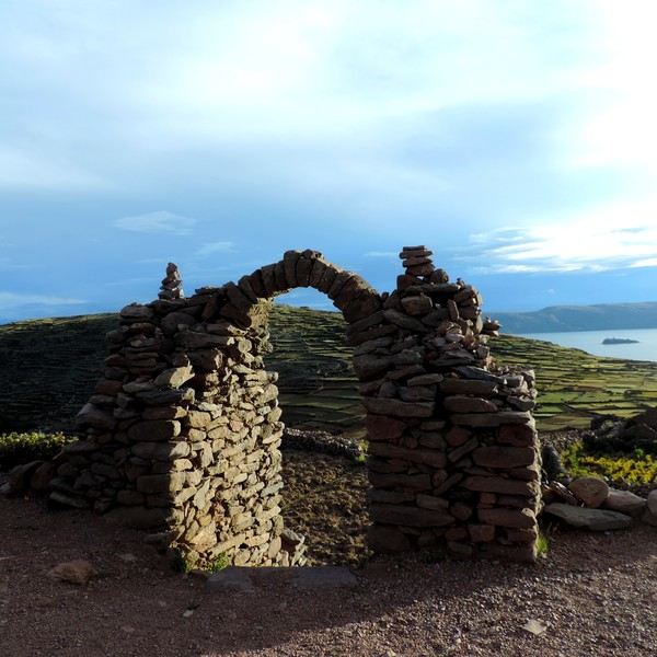 Arche de pierre donnant sur des cultures en terrasse