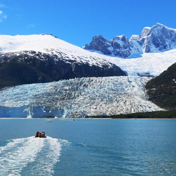 Canot à moteur navigant en direction d'un énorme glacier surmonté d'une chaîne de montagnes