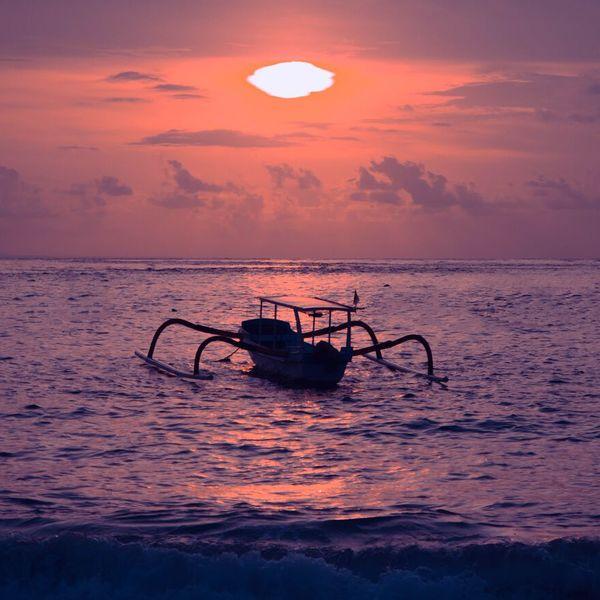 Silhouette de barque traditionnelle dans la lumière du coucher de soleil