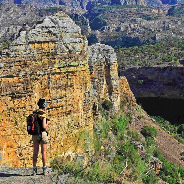 Une randonneuse face au massif rocheux