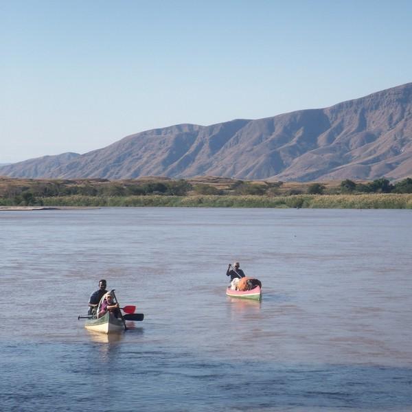 Deux canoë sur une large rivière et des montagnes à l'horizon