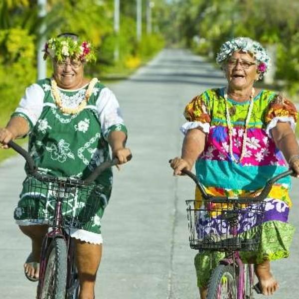 Deux femmes coiffées de fleurs sur leur vélo