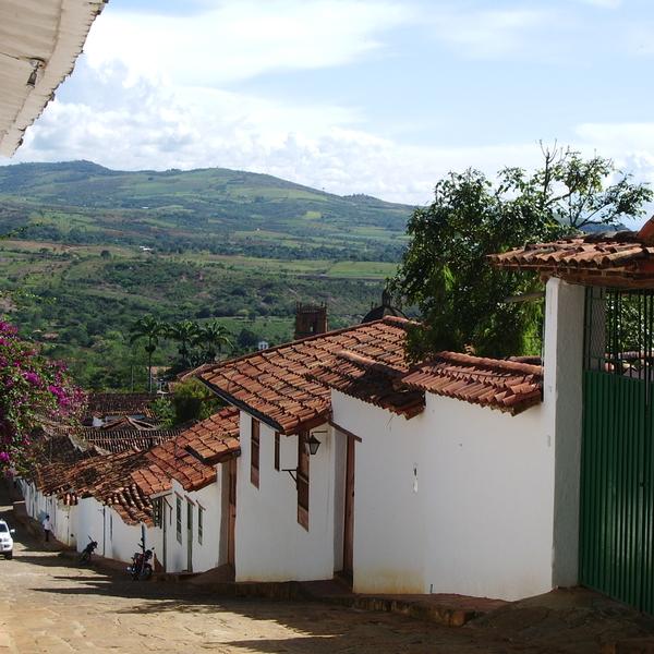 Ruelle en pente bordée de murs blancs avec au loin paysage de collines verdoyantes