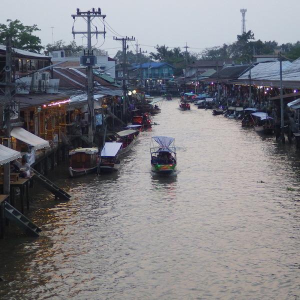 Vue sur un khlong bordé de barques traditionnelles et de petites maisons