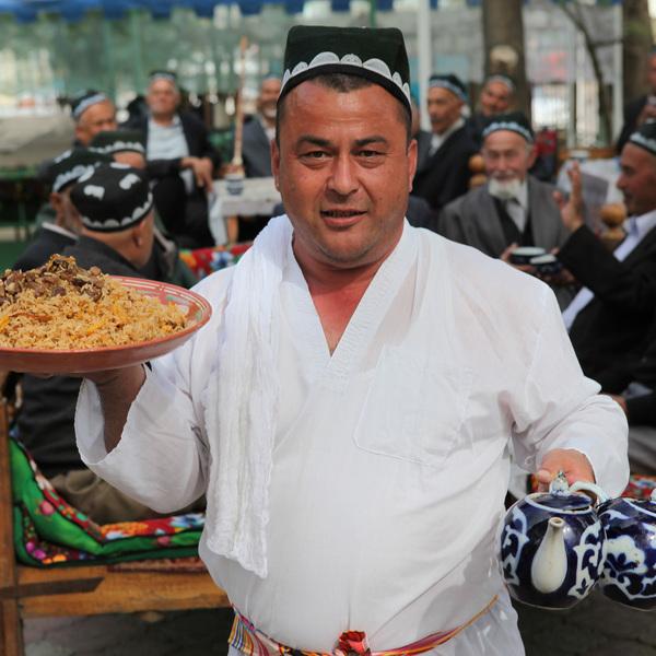 Un homme en costume traditionnel avec une théière et un plat de viande à la main