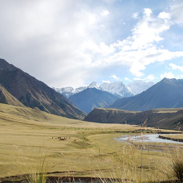 La vallée de Jayloo traversée par une rivière, avec les montagnes enneigées au loin