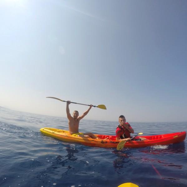 deux hommes dans un kayak sur une mer calme