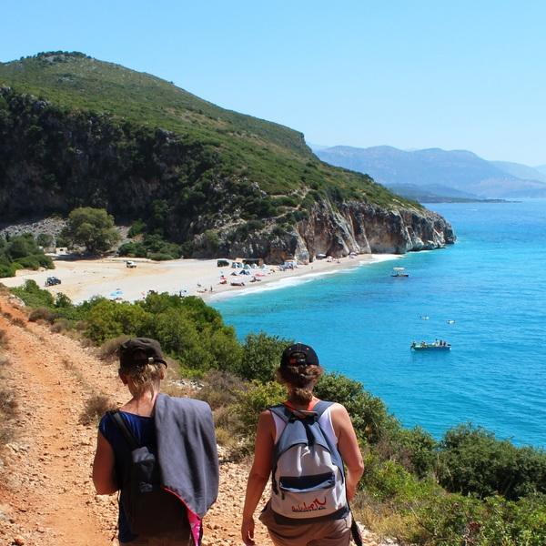 Deux personnes de vue marchant sur un chemin descendant vers la baie de Gjipe
