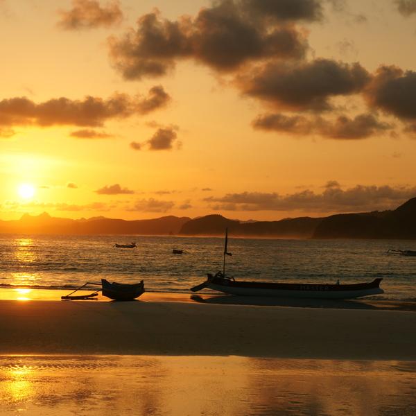 Barques échouées sur la plage à l'heure du coucher du soleil