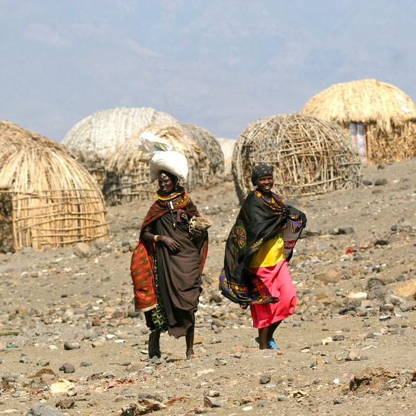 Deux femmes marchant devant un village de huttes en roseaux