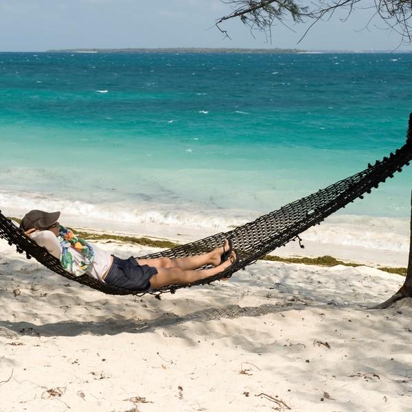 Personne se reposant dans un hamac sur une plage