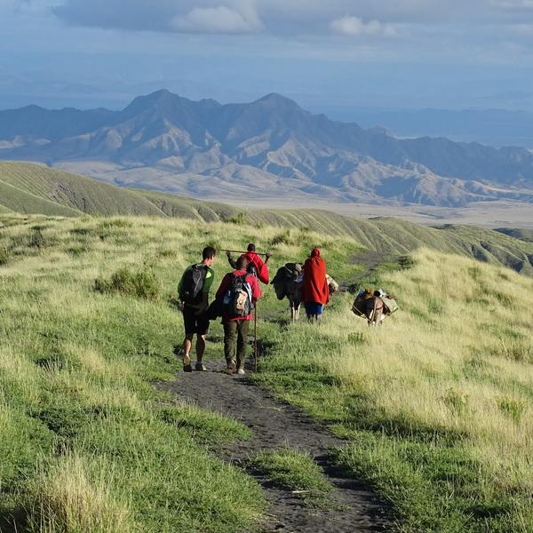 Randonneurs sur une piste avec guides masaïs et paysage montagneux au fond