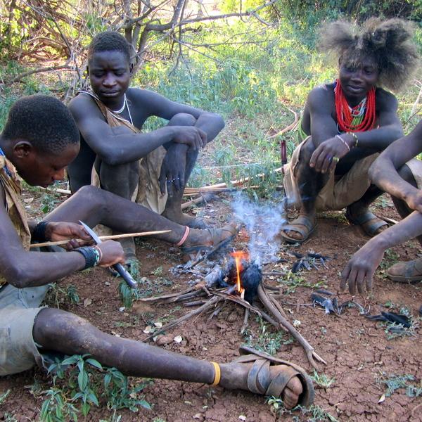Jeunes hommes noirs autour d'un feu de bois