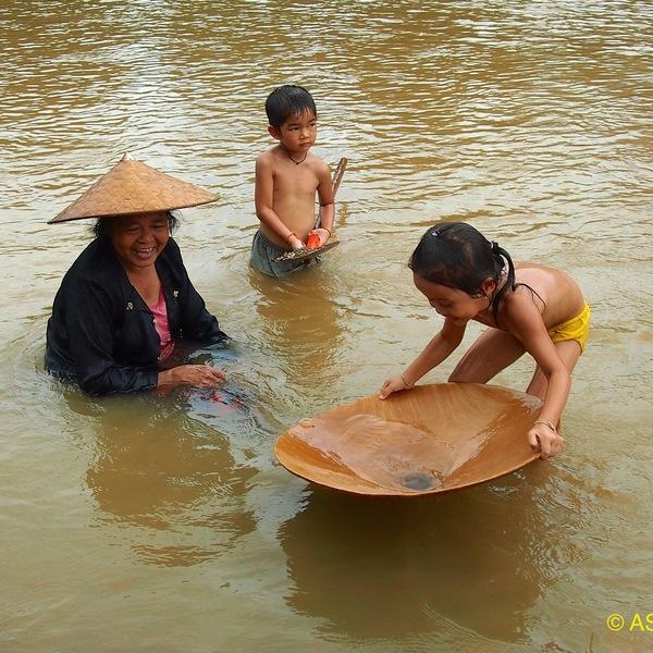 Une femme coiffée d'un chapeau traditionnel et ses enfants se baignant dans une rivière