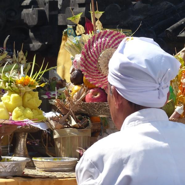 Un prêtre balinais vêtu de blanc devant des offrandes