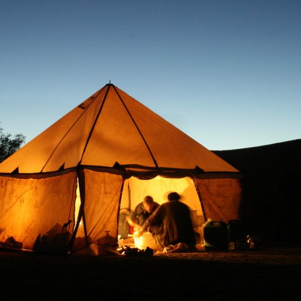 Das Bild zeigt ein Zelt bei Nacht, dass in der Wüste liegt.