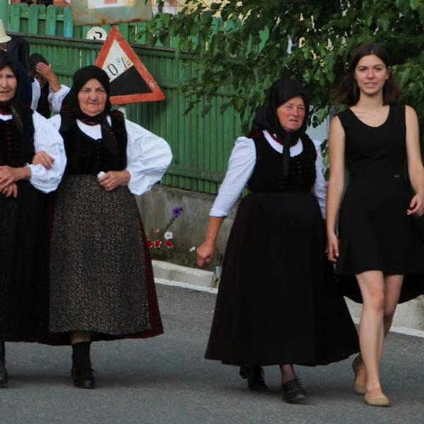Jeune fille en robe courte marchant à côté de vieilles dames en habit traditionnel