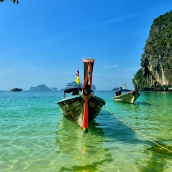 Pirogue traditionnelle amarrée sur les eaux turquoises de la plage à Koh Hong