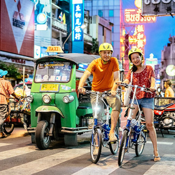 Couple de touristes se baladant dans Bangkok à vélo