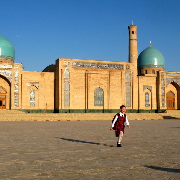 Un petit garçon courant sur le parvis de la mosquée Teleshayakh