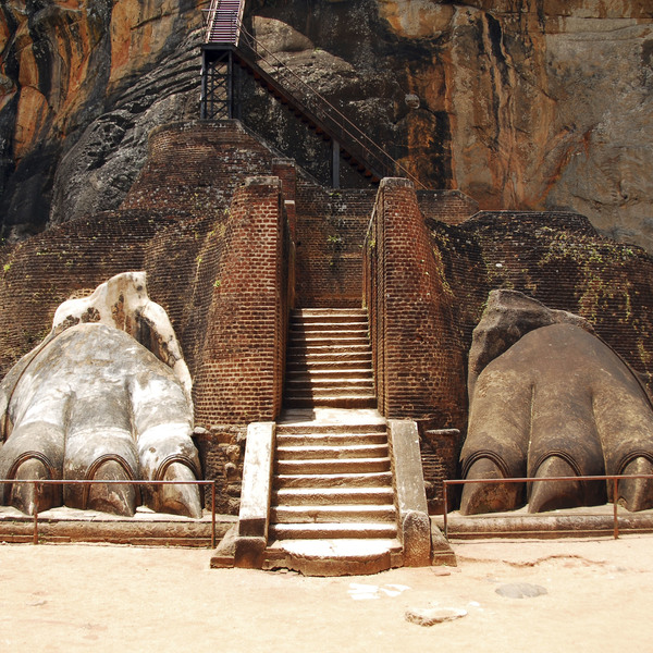 Escalier montant entre deux pattes griffues sculptées au pied d'un rocher