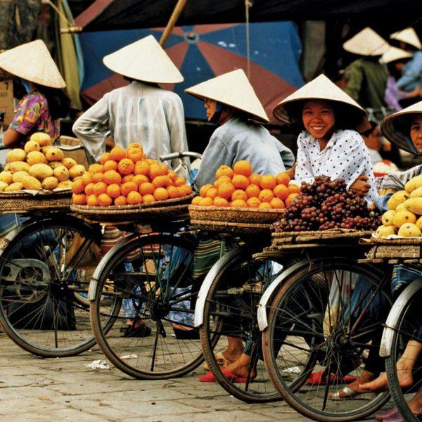 Vietnamiens coiffés de leur chapeau traditionnel attendant à côte de leurs bicyclettes chargées de fruits et légumes
