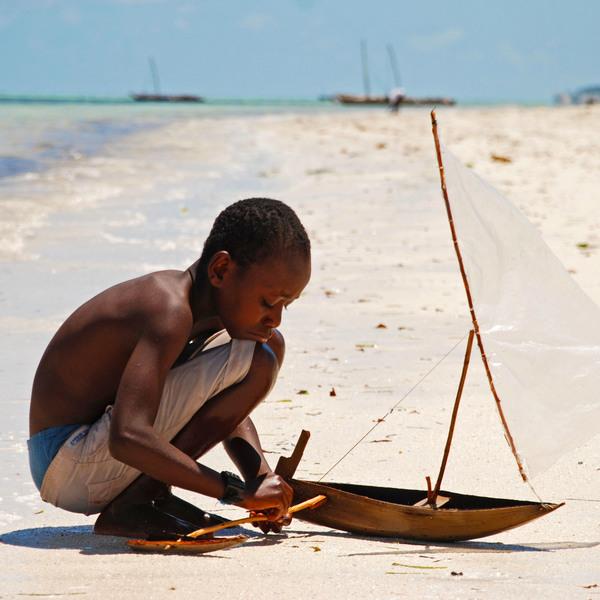 Arena blanca, niño jugando y agua turquesa en las maravillosas playas de Zanzíbar