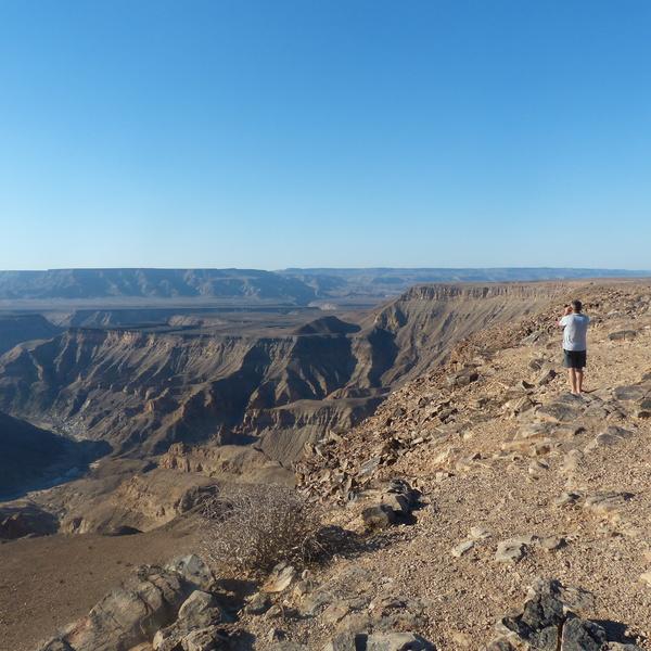 Un homme photographiant un vaste paysage de canyon