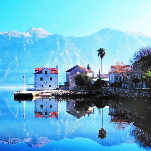 Petit port se reflétant dans l'eau et dominé par une chaîne de montagnes
