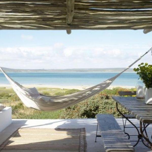 Table et hamac sous une pergola avec la mer à l'horizon