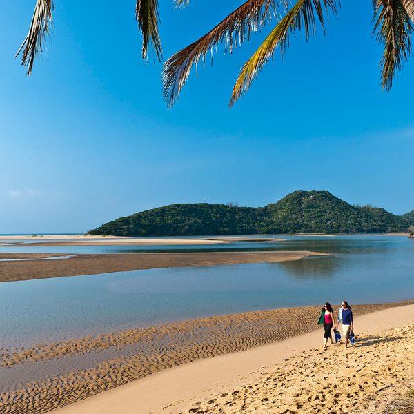Deux personnes marchant sur une plage et paysage de dunes