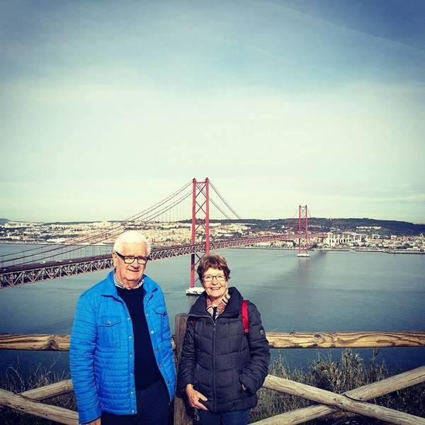 Couple de voyageurs posant devant le pont du 25 avril à Lisbonne