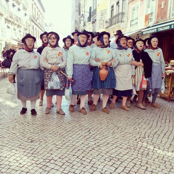 Groupe de femmes en tablier et chapeau noir chantant dans la rue
