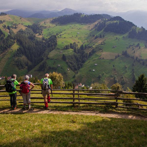 Des randonneurs sur une chemin avec le village de Moieciu de Sus en contrebas