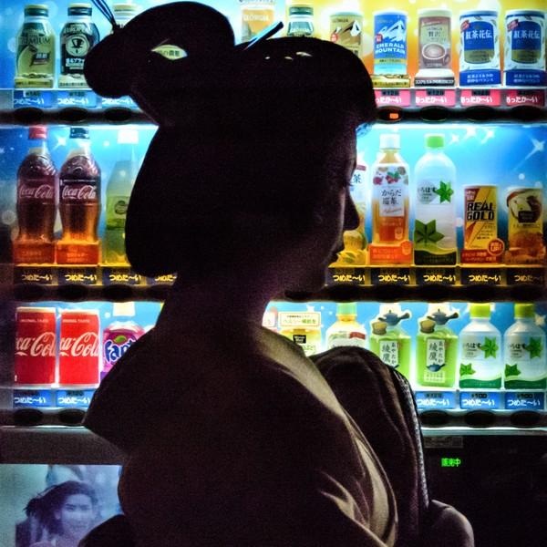 La nuit à Kyoto, une geisha passe en face d'une multicolore machine à boisson.