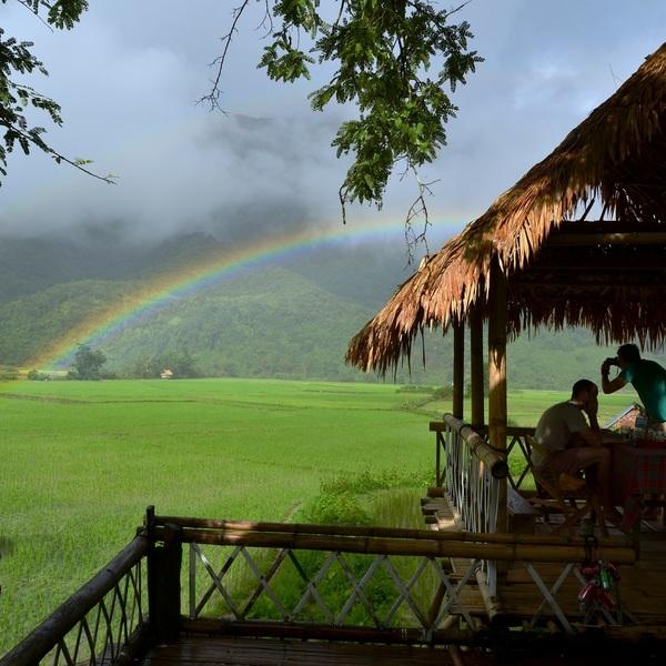Silhouettes de voyageurs admirant un arc-en-ciel sur les rizières depuis la terrasse de leur maison d'hôte
