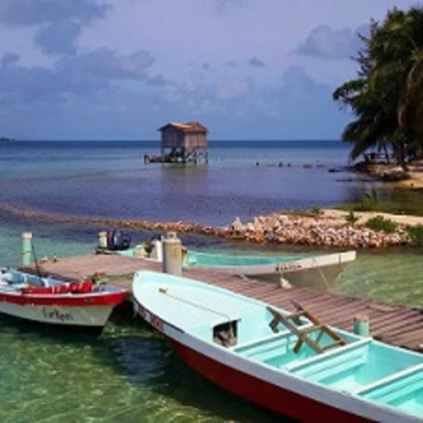 Barques amarrées à un ponton devant les eaux calmes d'un lagon
