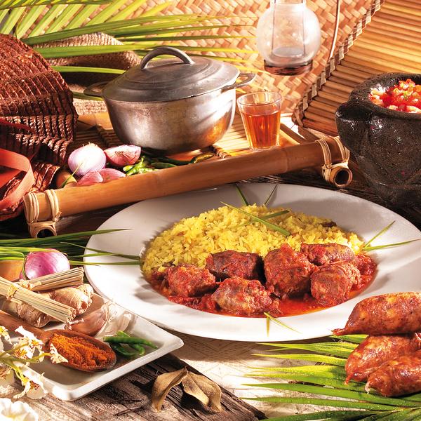 Table dressée avec plats typiques créoles et verre de rhum arrangé