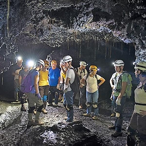 Groupe de visiteurs casqués et équipés dans un tunnel de lave
