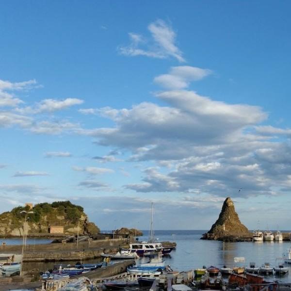 Un petit port de pêche avec deux gros rochers à l'entrée