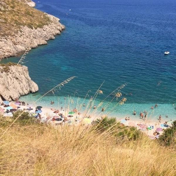 Vue sur une petite plage baignée par des eaux bleu marine