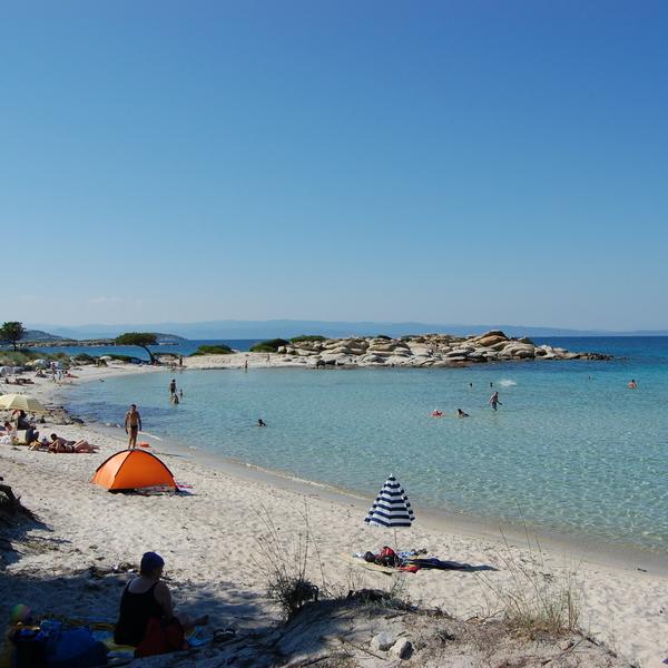 Vacanciers sur une plage bordée par une mer transparente