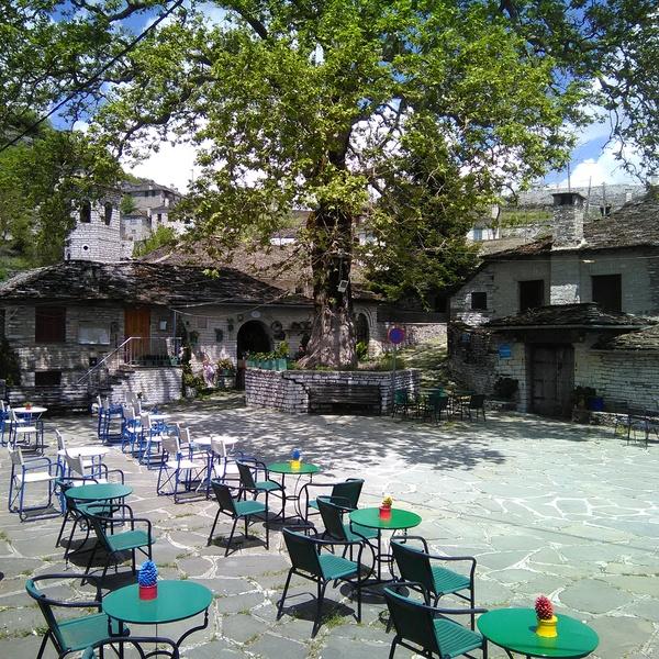 Une place de village avec des tables de café à l'ombre d'un arbre