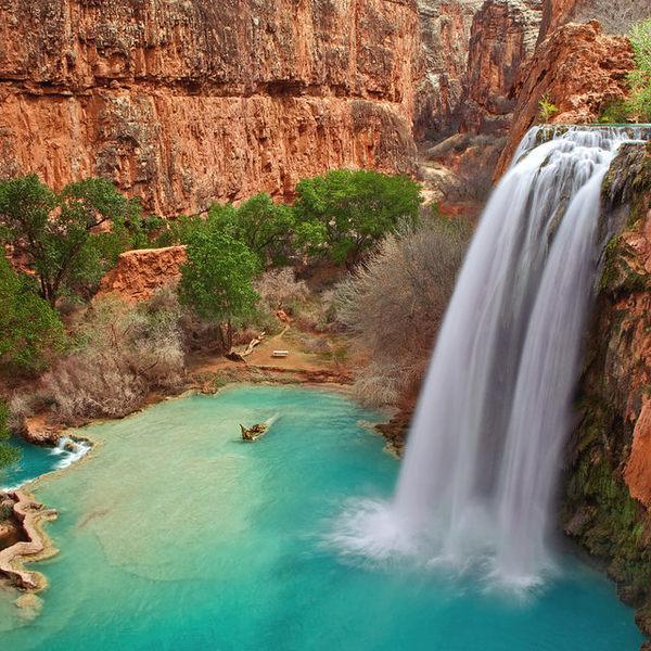 Au coeur d'un canyon aux roches rouges, une chute d'eau se jette dans une vasque naturelle aux teintes turquoises