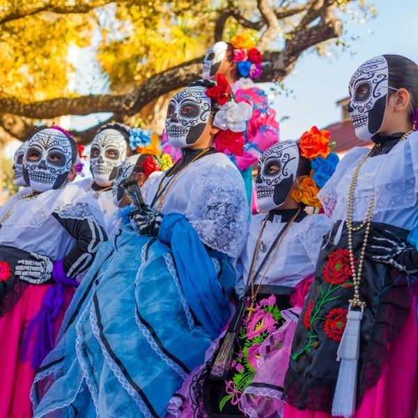 Das Bild zeigt mexikanische Frauen, die traditionelle Kleidung und bunte Masken tragen.