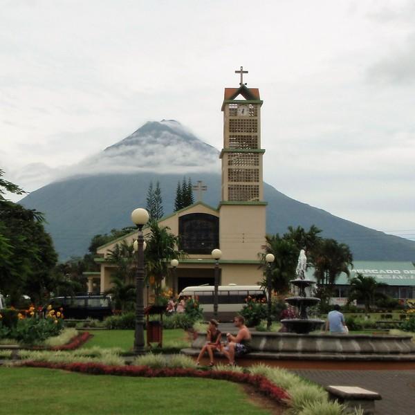 Place de village avec une église dominée par un grand volcan