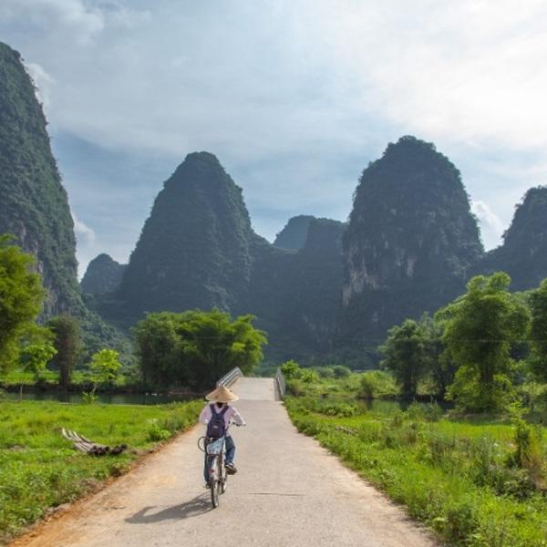 Un cycliste sur une route en direction de montagnes en forme de pain de sucre