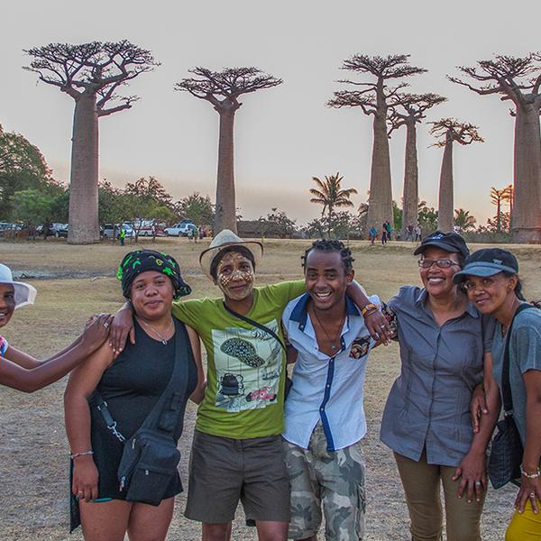 Groupe de Malgaches devant l'allée des Baobabs en soirée