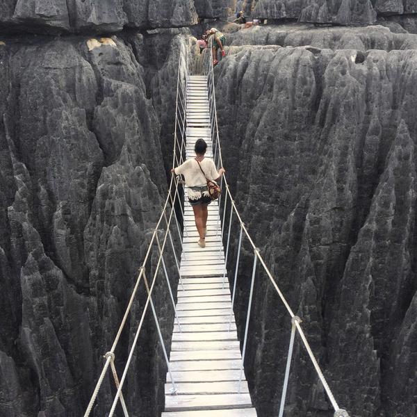 Une voyageuse traversant une passerelle pour rejoindre les Tsingi