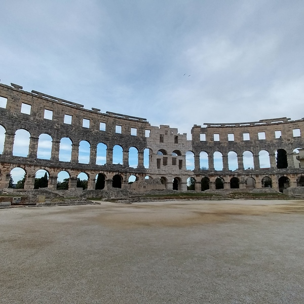 Standing in the middle of Arena in Pula Amphitheater, reminiscence of the Roman architecture